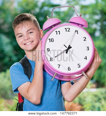 Outdoor portrait of happy teen boy 12-14 year old with big alarm clock. Back to school concept.