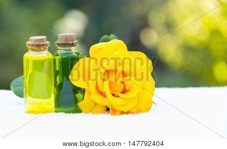 Essential oils for aromatherapy. Rose oil and green elixir. Useful Natural cosmetics. Cosmetics for saunas and spa treatments. Spa concept. Fragrant yellow rose. Copy space.