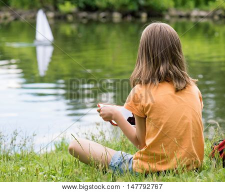 Girl playing with a remote controlled boat. Handmade model sailboat on lake - child is playing with tablet.