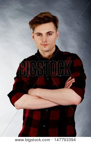 Young confident man with crossed arms.