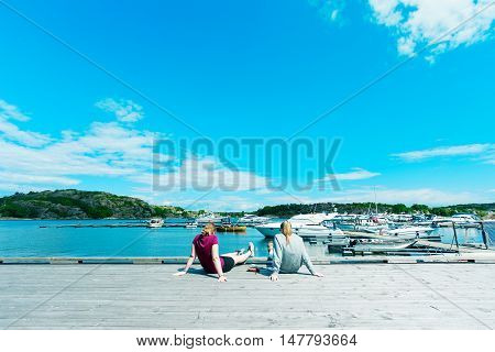 Two female students in shorts resting on the berth in port. Norway