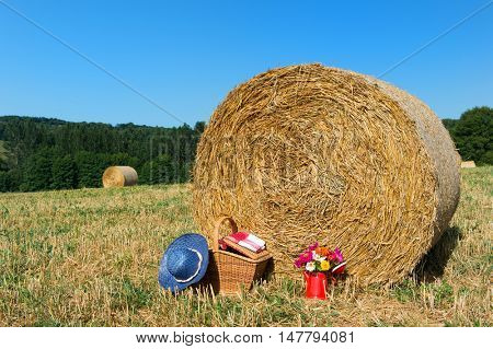 Bouquet garden flowers picnic basket and summer hat on hay roll in summertime
