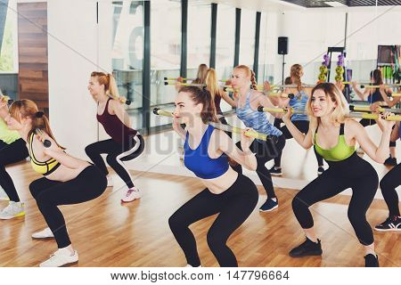 Squats with weights on training. Group of young women in aerobics class making exercises. Girls do squats with barbells. Healthy lifestyle in fitness club