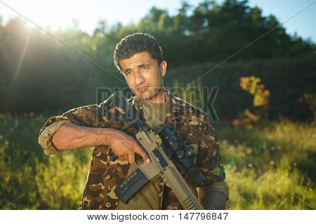 Man of Arab nationality in camouflage with a shotgun in an outdoor