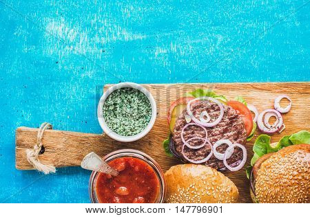 Homemade beef burgers with onion, fresh vegetables and tomato sauce on serving wooden board over blue painted background. Top view, copy space