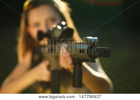 A young girl with a gun for trap shooting aiming at a target. Short depth of field focus on the barrel