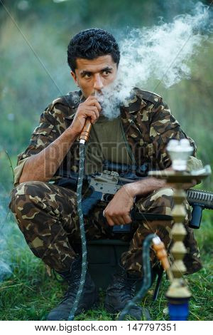 Man of Arab nationality in camouflage with a shotgun smokes a hookah outdoor