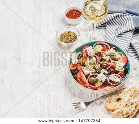 Greek salad with bread, oregano, pepper and glass of white wine over old white painted wooden board, top view, selective focus, copy space