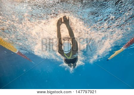 Female swimmer swims in back crawl style underwater in the swimming pool outdoors. She wears a black-lime swimsuit, a white swim cap and swim glasses. Sunlight falls from above. Horizontal.