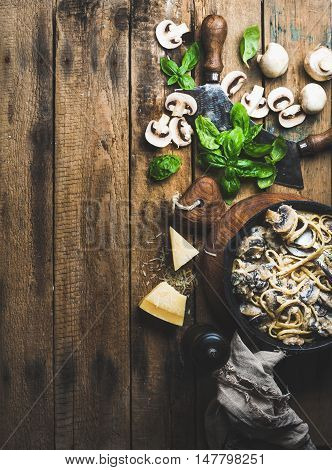Italian style dinner. Homemade creamy mushroom pasta spaghetti in cast iron pan with Parmesan cheese, fresh basil leaves and pepper over old rustic wooden background. Top view, copy space, vertical