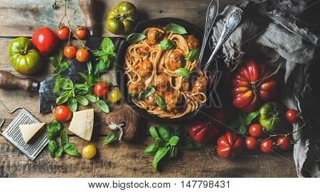 Italian pasta spaghetti with tomato sauce and meatballs in cast iron pan served with Parmesan cheese, fresh basil and colorful tomatoes over old rustic wooden background. Top view, horizontal