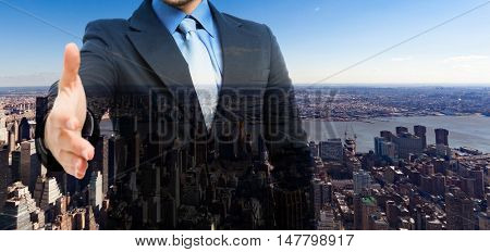 Double exposure of a businessman offering an handshake in front of New York City