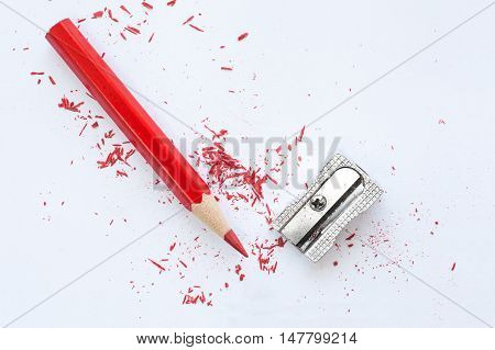 Red Wooden Pencil, Pencil Shavings And Sharpener On White