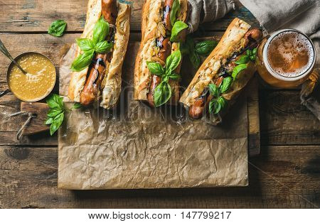 Glass of wheat unfiltered beer and grilled sausage dogs in baguette on baking paper with mustard, caramelised onion and herbs on serving board over rustic wooden background, top view, copy space