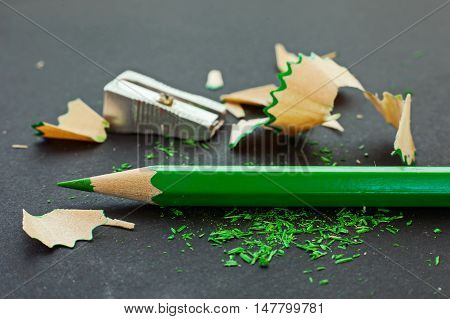 Green Colored Pencil, Pencil Shavings And Sharpener On Black