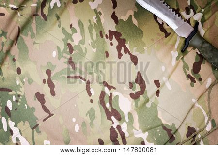 Combat knife on military camouflage fabric background concept