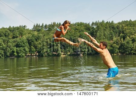 Father in the lake throwing his daughter into the water and having fun in summer