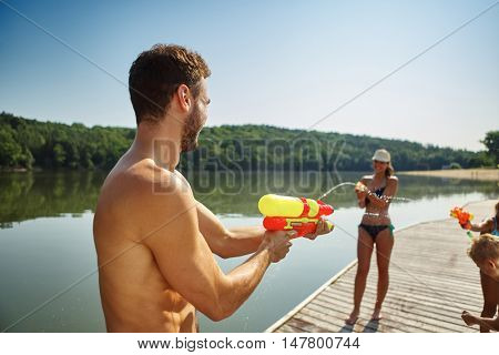 Family having fun and spraying each other with squirt guns in summer