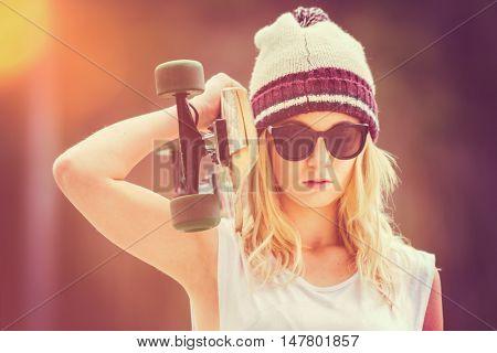 Pretty blond teen girl holding skateboard