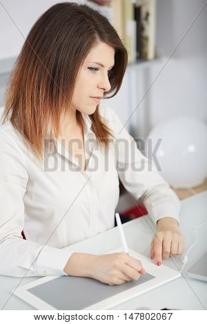 Young graphic designer working on coputer using tablet at home