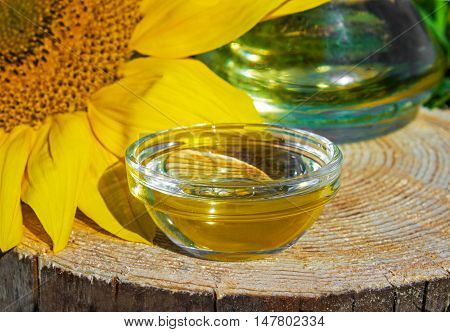 oil in jars and sunflower on wooden backgraund