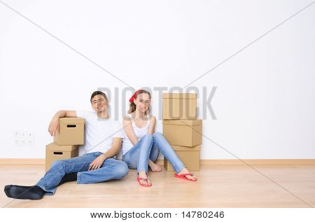 Joven pareja descansando de mudarse a una casa nueva. Espacio de gran copia.