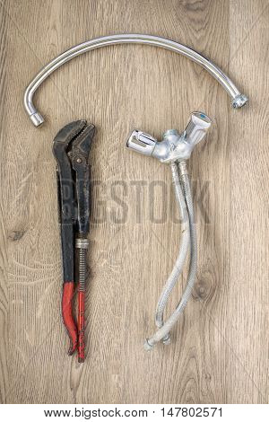 Rusty old plumbing wrench and tap on wooden background
