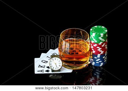 Cards with colorful chips to play poker and tumbler of whiskey with clock