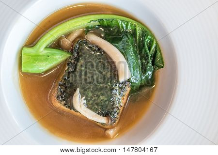 baked homemade tofu with kale and mushroom in gravy sauce