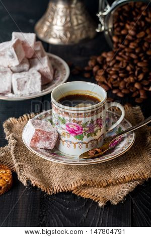 Antique set of Turkish coffee with Turkish delight on black wooden table close-up