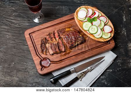Close up sliced medium rare grilled Beef steak Ribeye with cucumber and radish on cutting board on black background, top view