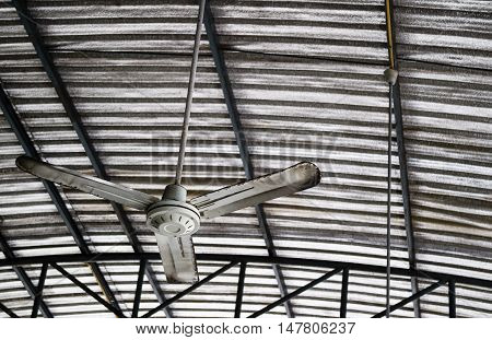 Old rusty gray metal ceiling fan hang on warehouse ceiling which covered with insulator to reduce temperature.