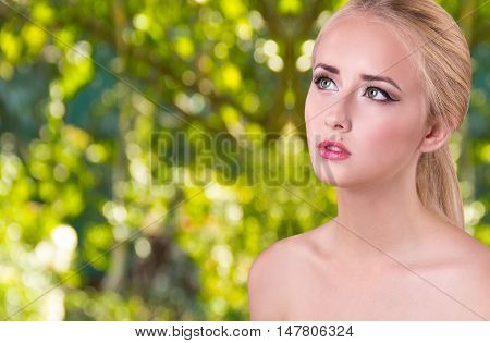 Beautiful young woman with green eyes and healthy skin. Portrait of the sensual girl on a background of green nature. Beauty Woman face Portrait. Spa concept. Copy space.