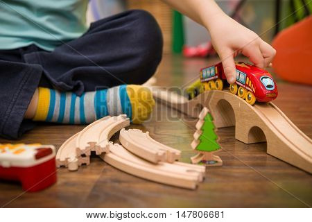 Close up on child's hands with toy train and railway in his room. Boy playing indoors.