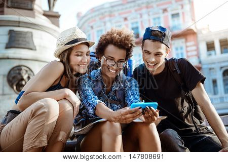 Young beautiful friends travelers with backpacks smiling, making selfie, sitting near sight.