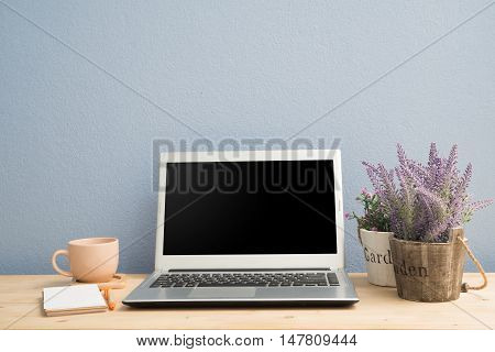 Office desk with laptop black coffee Notepad paper lavender flower and pink rose flower on flower pot. View from above notebook.