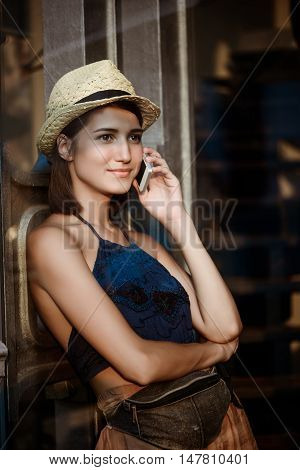 Young beautiful brunette girl in hat smiling, speaking on phone. Shot from outside.