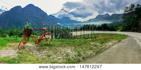Lonely red decorative bicycle stands on a hillside, Geirangerfjord