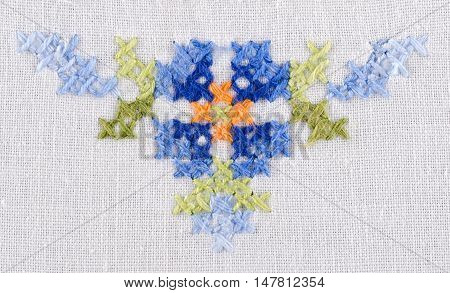 Blue flower triangle motiv hand embroidery on white linen tablecloth.  Multicolored cross stich decoration with yarn. Handicraft. Macro photo close up from above.