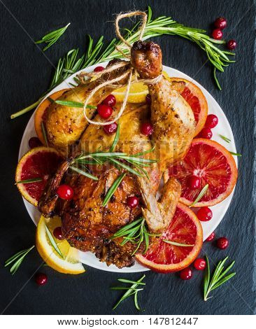Roasted whole chicken on white plate on stone dark background. Served with red oranges lemon rosemary and cranberries. Top view.