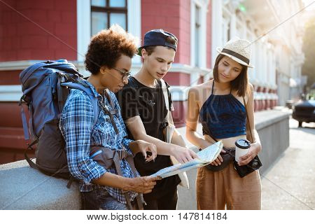 Friends travelers with backpacks smiling, looking route at map outdoors.