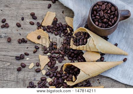Roasted coffee beans in a ceramic mug and sugar waffle cones on a wooden background