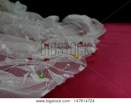 beautiful white lace laid in a pleated red silk with multi-colored needles