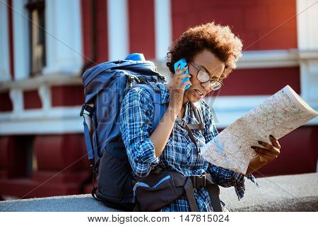 Young beautiful african female traveler with backpack speaking on phone, looking at map outside.