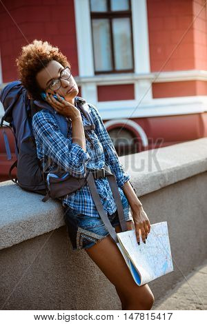 Young beautiful african female traveler with backpack speaking on phone, holding map outside.