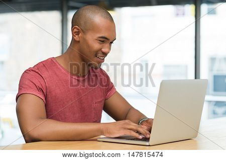 Young student working on laptop at internet cafe. Smiling african young man typing on laptop computer in a cafeteria. Smiling guy studying on laptop and surfing the web.