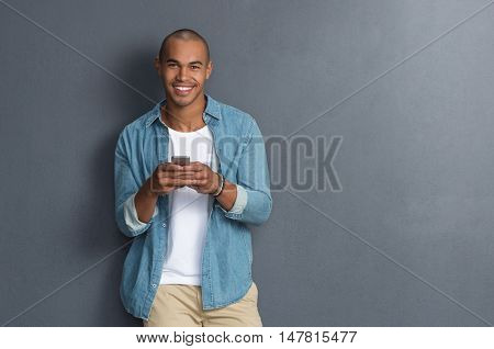 Young african man leaning against a grey wall using mobile phone. Portrait of a happy laughing guy texting a phone message and looking at camera. Man reading a message on cell phone with copyspace.