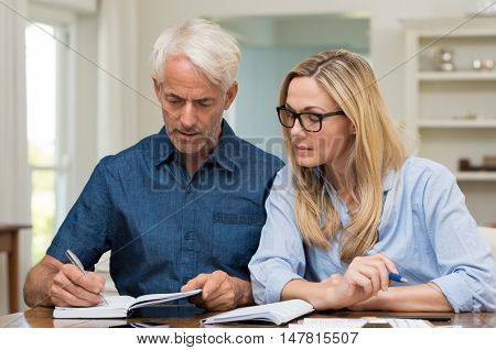 Mature couple calculating bills at home. Mature woman wearing spectacles discussing home economics. Senior man worried about financials at home while woman looking the bills.