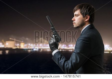 Secret Agent Holds Pistol With Silincer In Hand At Night.