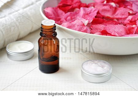 Aroma essential oil dropper bottle, different type skincare cream samples, bowl of pink rose petals.